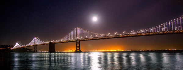 San Francisco Bay Bridge at night under a full moon